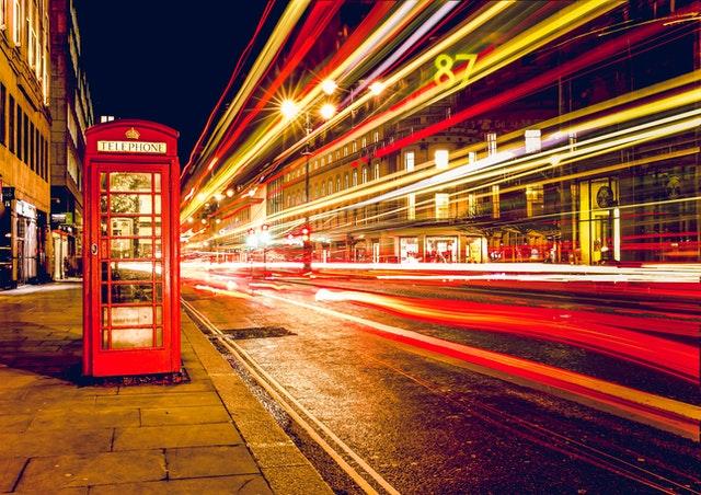 Cabine telefônica britânica com luzes ao fundo. 30 gírias Britânicas que você deveria começar a usar imediatamente.